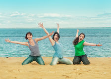 Three happy women sitting on the beach Royalty Free Stock Image