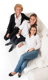 Three happy women on a sofa royalty free stock images