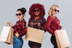 Three happy women in sunglasses. Afro american, asian and caucasian races. Shopping with isolated on gray background on. Beautiful young women make shopping in Royalty Free Stock Image