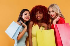 Three happy women in sunglasses. Afro american, asian and caucasian races. Shopping with isolated on orange background. Beautiful young women make shopping in Royalty Free Stock Photos