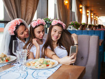 Three happy women taking selfie at hen party in cafe Royalty Free Stock Image