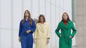 Three happy women walks runway in cashmere wool coats on the street. Slowly stock video footage