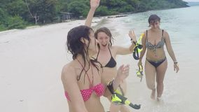Three happy women wearing bikinis partying at the beach going with snorkeling masks in their hands stock video