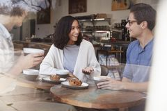 Three happy young adult friends sit talking at a coffee shop royalty free stock photography