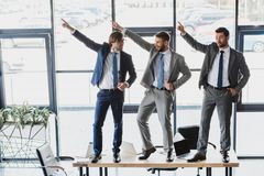 three happy young businessmen dancing on table royalty free stock photography