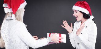 Three happy young girl in costume of Santa Claus with Christmas. Happy young girl in costume of Santa Claus with Christmas gifts. isolated on black.photo with Stock Photography