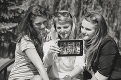 Three happy young girlfriends doing selfie by phone Royalty Free Stock Images