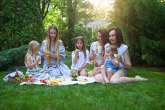 Three happy young mothers and daughters having picnic Stock Photography