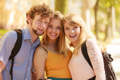 Three happy young people friends outdoor. Royalty Free Stock Image