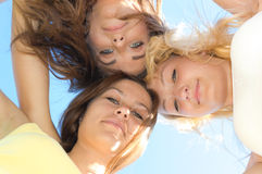 Three happy young woman friends looking down against blue sky. Three happy teen girls friends looking down against blue sky background Royalty Free Stock Photo