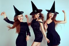 Three happy young women in black witch halloween costumes on party over blue neon background. Emotional young women dance. royalty free stock photos