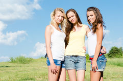 Three happy young women embracing against blue sky Royalty Free Stock Images