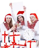 Three happy young women in hats of Santa Claus with clock and blank poster congratulating on Christmas . The concept of the celebration stock photography