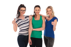 Three happy young women showing the ok thumbs up sign. Three happy young women showing the ok thumbs up hand sign on white background Royalty Free Stock Photography