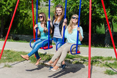 Three happy young women on swings Stock Image