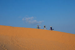 Three hawkers ( saleswomen ) carrying fast foods are walking on the sand hills at Mui Ne, Phan Thiet City, Binh Thuan, Vietnam Royalty Free Stock Images