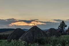 Three haystacks in the field and clouds in the sky royalty free stock image