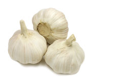 Three heads of dried garlic. On a white background Royalty Free Stock Photo