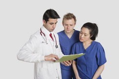 Three healthcare professional discussing medical report over gray background Royalty Free Stock Image