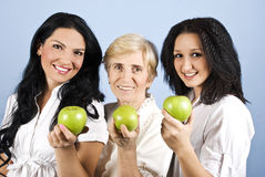 Three healthy beauty women giving you apples. Three healthy beautiful women ,mother and daughters standing in a line and showing or giving green apples,blue Stock Photo