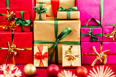 Three Heaps of Christmas Gifts Sorted by Color. Three piles of plain Xmas presents grouped by color. Red, gold and magenta. All with bow knots. Stars and baubles Stock Photos