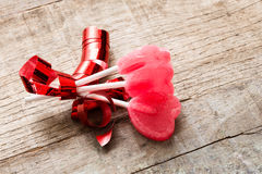 Three heart candies with bow over wooden background Royalty Free Stock Image