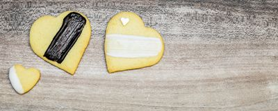 Three heart cookies, decoration with black and white glazing, ba. Nner with copyspace Royalty Free Stock Image
