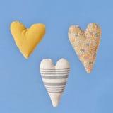 Three heart fabric on a light blue background. Stock Photos