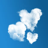 Three heart-shaped clouds on blue sky Stock Photos