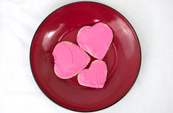 Three heart shaped cookies arranged on red plate Royalty Free Stock Photo