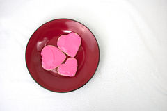 Three heart shaped cookies arranged on red plate Royalty Free Stock Photos