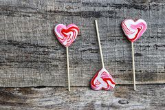 Three heart-shaped white-red lollipops on a wooden surface stock image