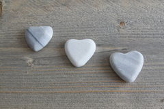 Three Heart of stone on wood background Stock Photo