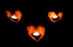 Three hearts. Three couples of heart-shaped palms with candles on black background Stock Photo