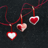 Three hearts of fabric on a black background. Symbol of love. Stock Photos
