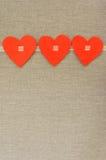 Three hearts. From felt gray background stock photos
