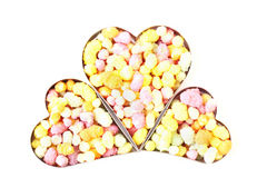 Three hearts filled with candy. Three metal hearts filled with candy isolated on a white background Royalty Free Stock Photos