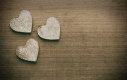 Three hearts on a grungy wooden background Stock Photos