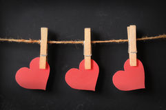 Three hearts hanging on blackboard. Background Stock Photography