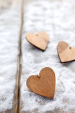 Three hearts with inscriptions of love on the background of the boards is not the background of snow, Valentine`s day Stock Images