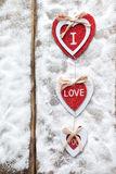Three hearts with inscriptions of love on the background of the boards is not the background of snow, Valentine`s day Royalty Free Stock Images