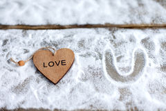 Three hearts with inscriptions of love on the background of the boards is not the background of snow, Valentine`s day Royalty Free Stock Photo