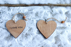 Three hearts with inscriptions of love on the background of the boards is not the background of snow, Valentine`s day Royalty Free Stock Photos