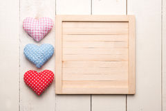 Three hearts on wood background Stock Images