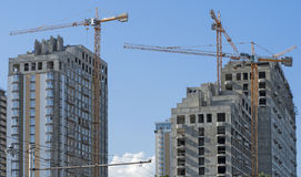 Three high-rise buildings and cranes against the sky Royalty Free Stock Images