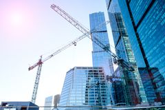 Three high-rise crane against the background of a glass skyscraper building. Impressive reflection and glare from the sun. Three high-rise cranes against the royalty free stock photo