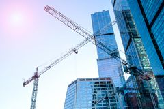 Three high-rise crane against the background of a glass skyscraper building. Impressive reflection and glare from the sun. Three high-rise cranes against the stock images