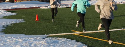 Three girls running on a turf field with snow on it. Three high school girls sprinting on a green turf field on the spots that di not have snow on them royalty free stock image