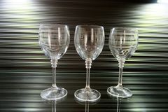 Three high transparent glasses on a beautiful brown background royalty free stock photos