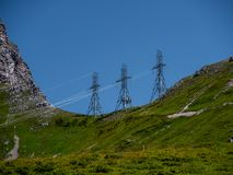 Three high voltage post power poles high up in the mountains high voltage tower switzerland alps. Sunny royalty free stock image